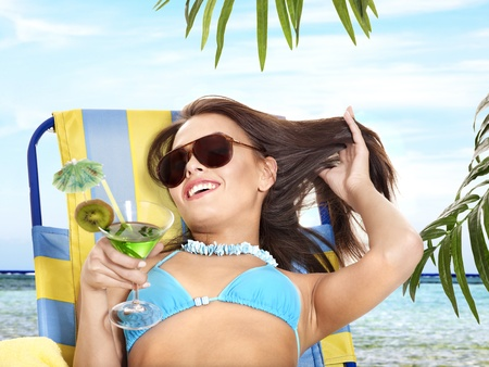 Girl in bikini drink juice through a straw. Outdoor. photo