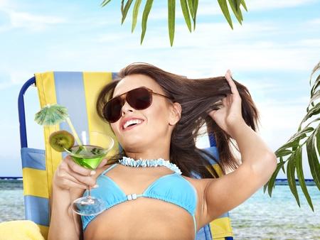 Girl in bikini drink juice through a straw. Outdoor. Stock Photo - 12341178