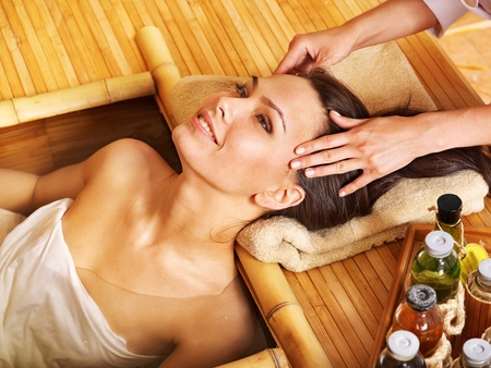 head massage: Young woman getting head massage in bamboo spa. Stock Photo