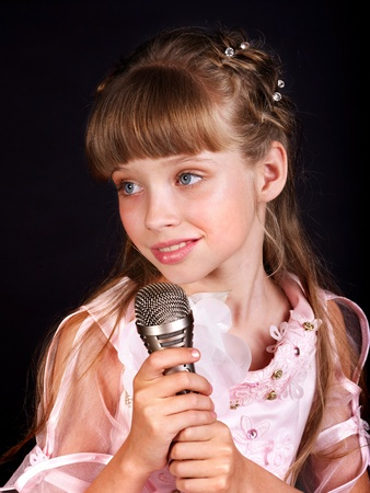 Singing of little girl in microphone. photo