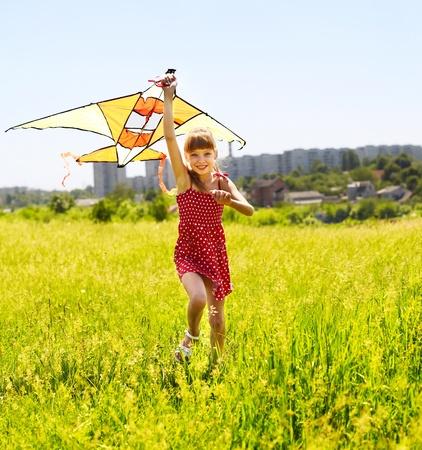 Child flying kite outdoor. little girl running across  green grass. photo