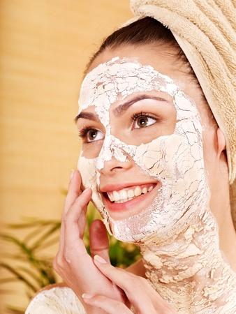 Beautiful girl having clay facial and body mask apply by beautician. photo
