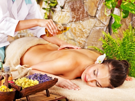 massage oil: Young woman getting massage in spa.