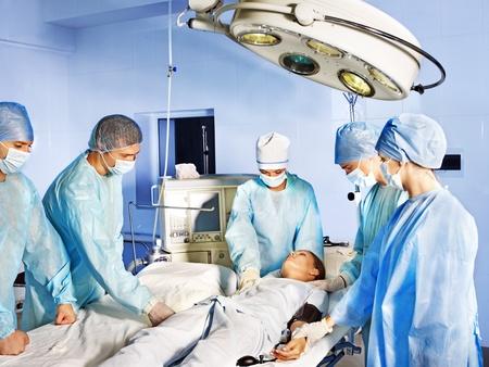 paciente en camilla: Grupo de cirujano y el paciente en la sala de operaciones.