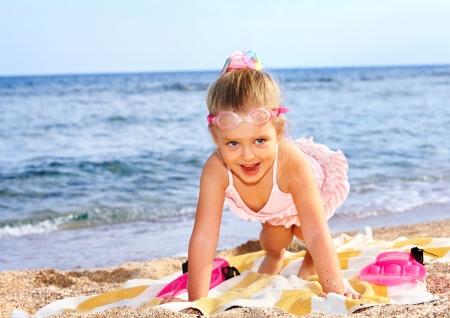 swim mask: Little girl  playing on  beach.