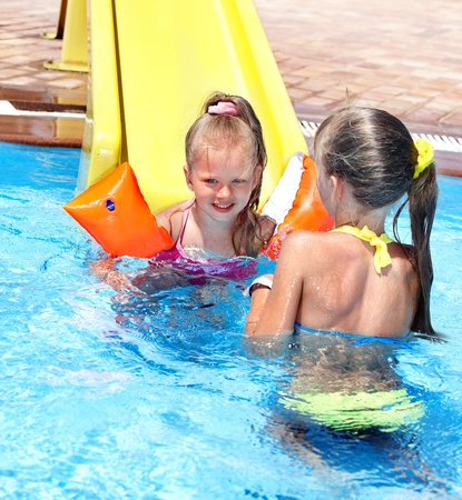 wet bikini: Children on water slide at aquapark. Summer holiday. Stock Photo