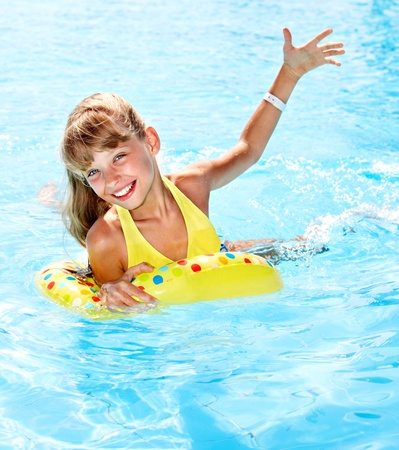 one piece swimsuit: Child sitting on inflatable ring in swimming pool.