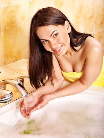 tap room: Woman washing hand in bathroom.