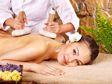 day spa: Young woman getting massage in bamboo spa.