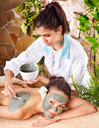 Beautiful girl having clay facial mask apply by beautician. photo