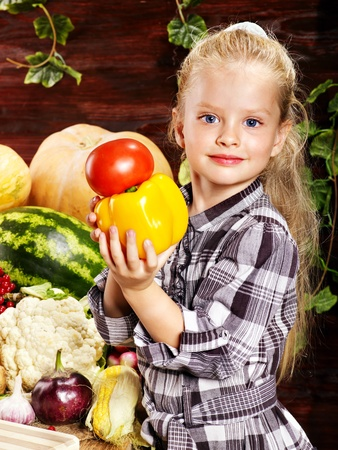 the corn salad: Little girl with vegetable on kitchen. Stock Photo