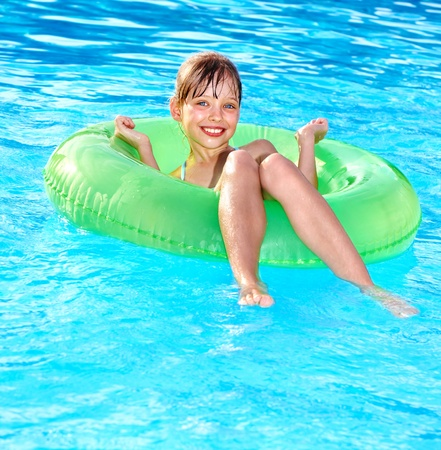 float tube: Little girl sitting on inflatable ring in swimming pool.