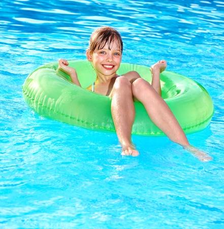Niña sentada en el anillo inflable en la piscina.