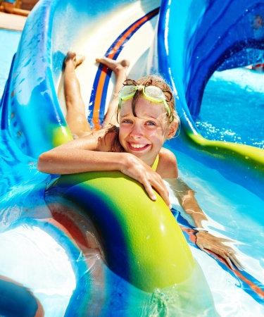 Child on water slide at aquapark  Summer holiday  Stock Photo