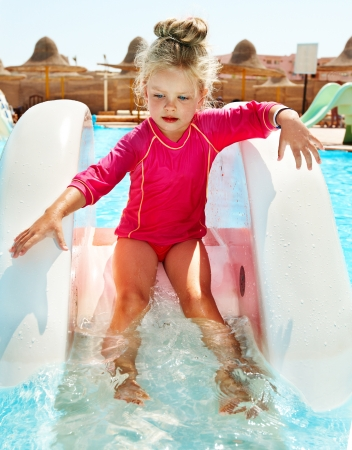little girl swimsuit: Child on water slide at aquapark. Summer holiday.