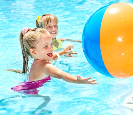 ball on water: Little girl  swimming in pool. Stock Photo