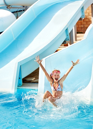 Child on water slide at aquapark. Summer holiday. photo