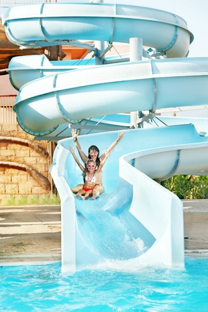 blue bikini: Child with mother on water slide at aquapark. Summer holiday.