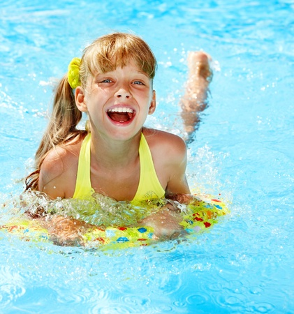 one piece swimsuit: Little girl sitting on inflatable ring. Stock Photo