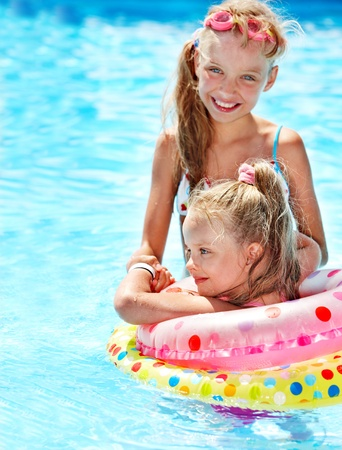 bambini seduti: I bambini seduti su anello gonfiabile in piscina. Archivio Fotografico