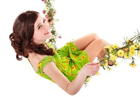 Beautiful girl swinging on flower swing. Isolated. photo