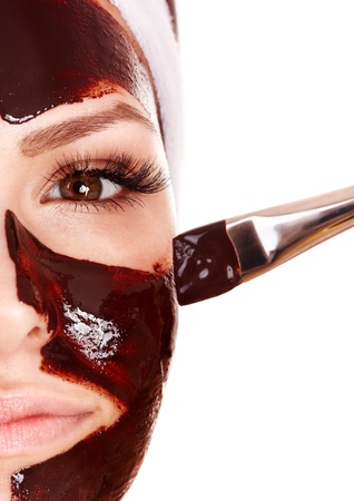 Girl having chocolate facial mask apply by beautician. Stock Photo