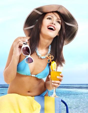 Girl in bikini on beach drinking cocktail. Outdoor. photo