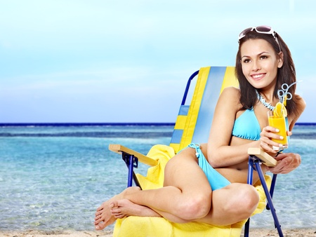 Girl in bikini drink juice through a straw on beach. Outdoor.