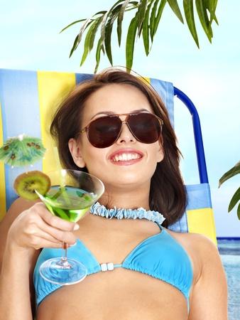 Girl in bikini drink juice through a straw. Outdoor. photo