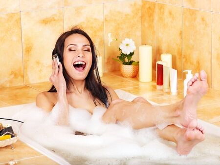 Young woman listening to music in bubble  bath. photo