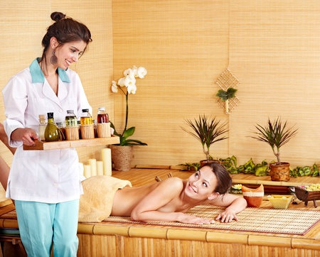 Beautiful young woman getting massage in spa. photo