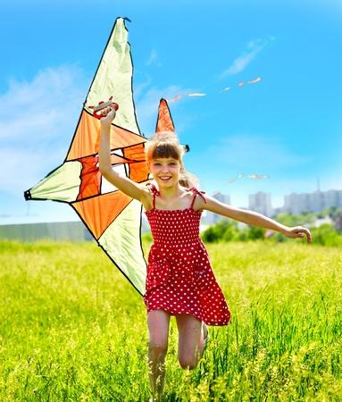 papalote: Ni�o vuelo de cometas al aire libre. ni�a corriendo por la hierba verde.