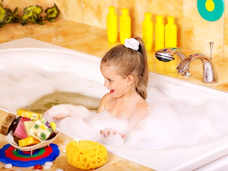 Child washing in bubble bath . photo
