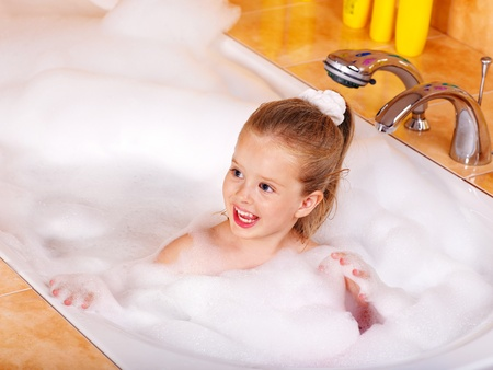 Little girl washing in bubble bath . photo