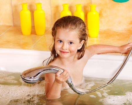 douche: Little girl washing in bubble bath .