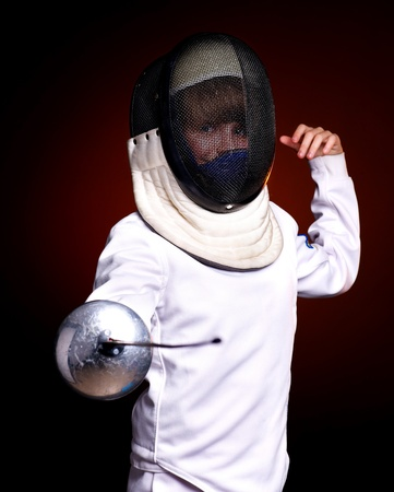 epee: Child epee fencing lunge. Dark background.