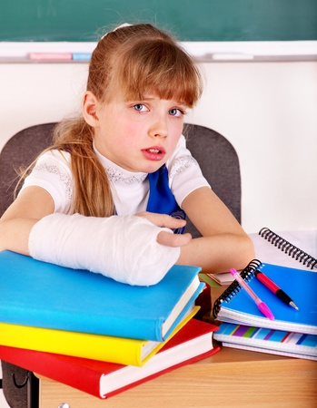 Disabled child with broken arm in classroom. photo