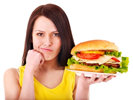 unhealthy living: Woman holding hamburger. Isolated. Stock Photo