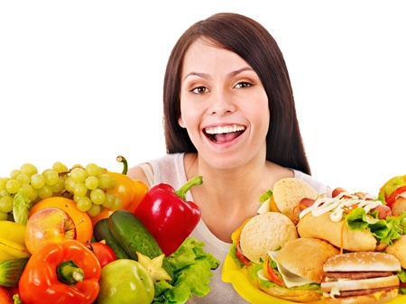 Woman choosing between fruit and hamburger. Isolated. Stock Photo - 13258381