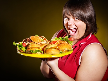 Overweight woman holding hamburger. Stock Photo - 13258974