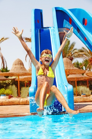 bikini wear: Child on water slide at aquapark. Summer holiday.