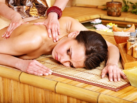 Young woman getting massage in bamboo spa. Stock Photo - 13308055