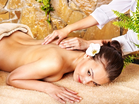 body oil: Young woman getting massage in spa.