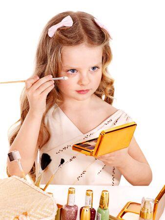 Child cosmetics. Little girl applying make up. photo