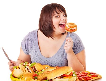 ätande: Kvinna äter snabbmat. Isolated. Stockfoto