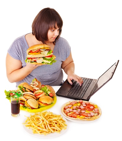 Woman eating fast food at work. Isolated. Stock Photo