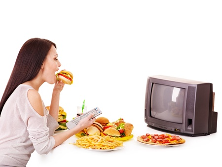 high calorie: Woman eating fast food and watching TV. Isolated. Stock Photo