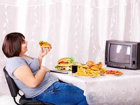fat girl: Overweight woman eating fast food and watching TV.