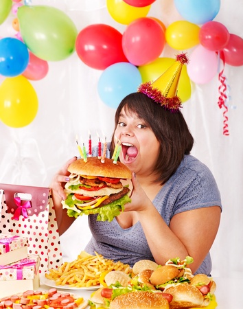 Woman eating hamburger at birthday. Isolated. photo