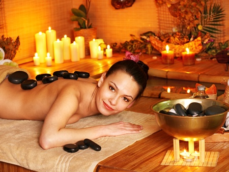 Woman getting stone therapy massage in bamboo spa. Stock Photo - 13308134